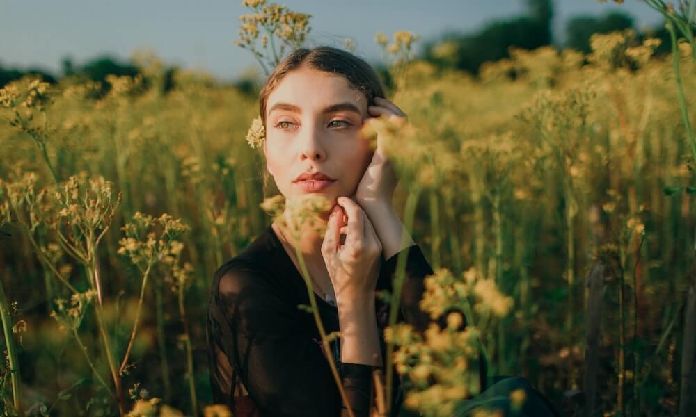 woman sitting in field of flowers